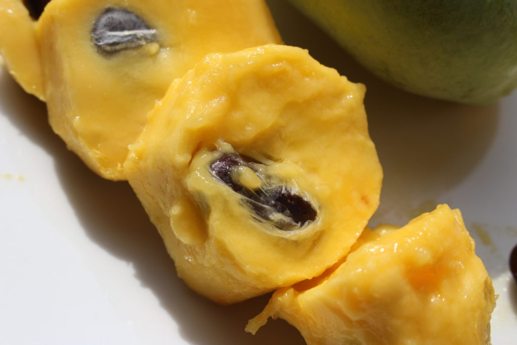 A close up of cut-up cross-sections of a pawpaw which have had the skins removed.