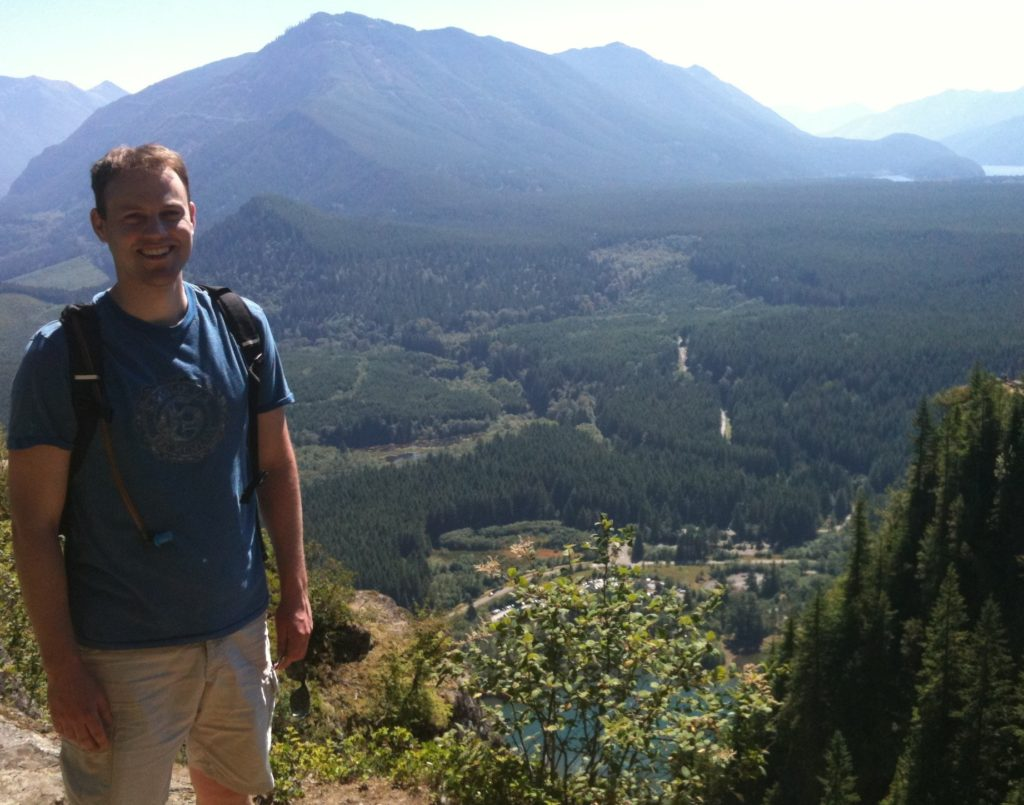 James Amadon stands on Rattlesnake Ledge with a small mountain range in the distance and a forested valley floor just behind him.